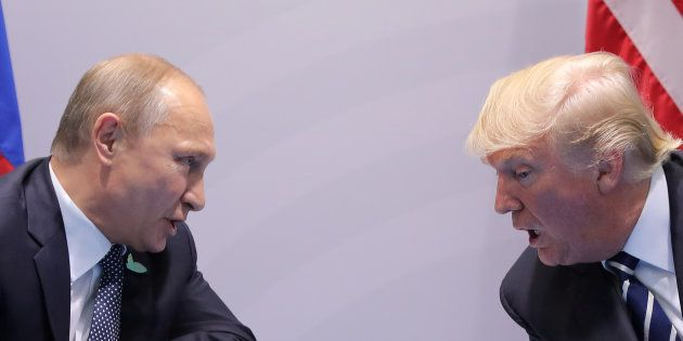 Russia's President Vladimir Putin talks to U.S. President Donald Trump during their bilateral meeting...