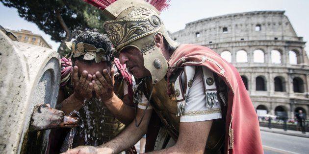 Due centurioni si rinfrescano ad una fontanella davanti il Colosseo per l'ondata di caldo nord africano...