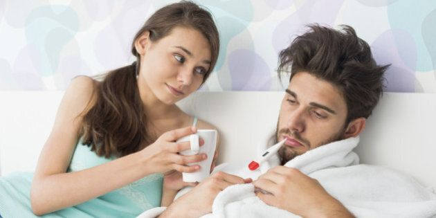 Young woman giving coffee mug to man with thermometer in