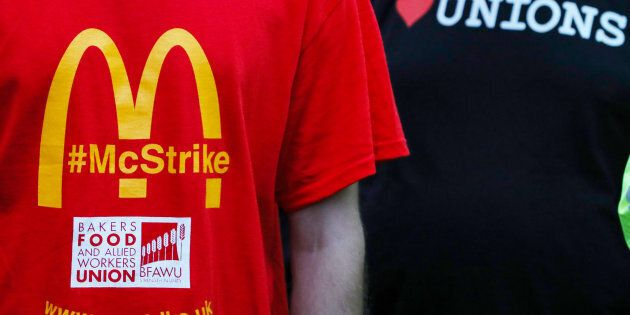 A member of staff wears a strike t-shirt as they listen to a speaker during a strike, the first industrial...
