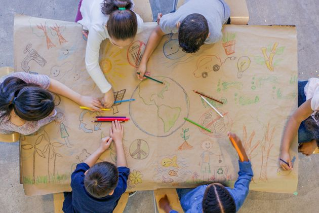 An aerial view of a multi ethnic group of children learn about going green and color in environmentally...