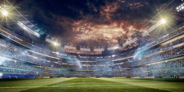 A wide angle of a outdoor soccer stadium full of spectators under a dramatic stormy evening sky at sunset....