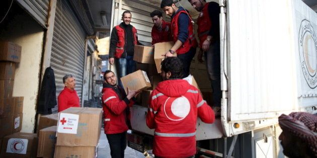 Red Crescent members unload aid boxes in the rebel held besieged city of Douma, a suburb of Damascus...