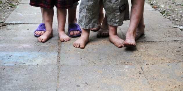 Homeless children with bare feet standing on a stone