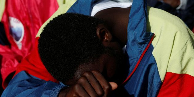 A migrant reacts as the Malta-based NGO Migrant Offshore Aid Station (MOAS) ship Phoenix arrives with...