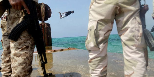 A man jumps into the sea as memebrs of Libyan National Army stand guard in Sabri, a central Benghazi...