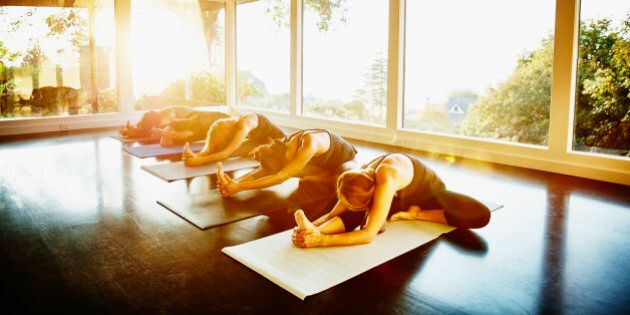 Women practicing yoga in studio in bend to right leg