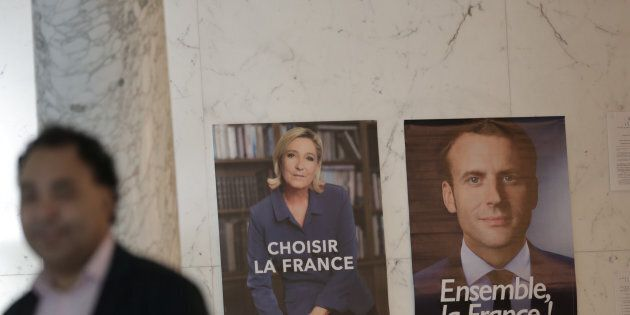 A poll worker stands next to posters for presidential candidates Marine Le Pen and Emmanuel Macron during...