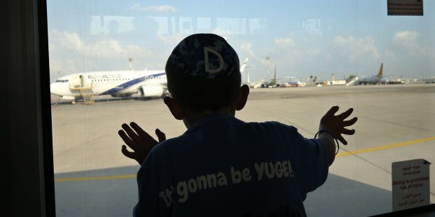 TOPSHOT - A child looks through the window of a bus as Jewish immigrants from the US, making Aliyah (Immigration...