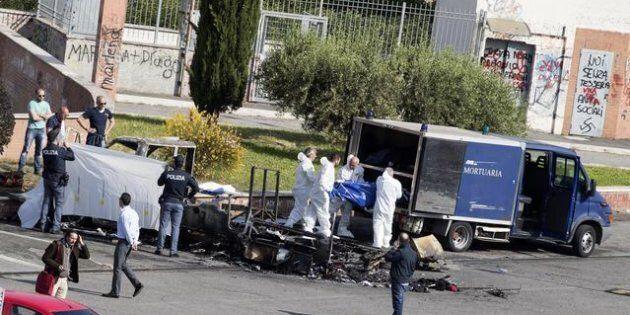 Il cadavere di una delle vittime del rogo sul camper viene trasferito sul furgone della polizia mortuaria...