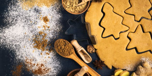 Christmas baking background with dough, cookie cutters and spices viewed from