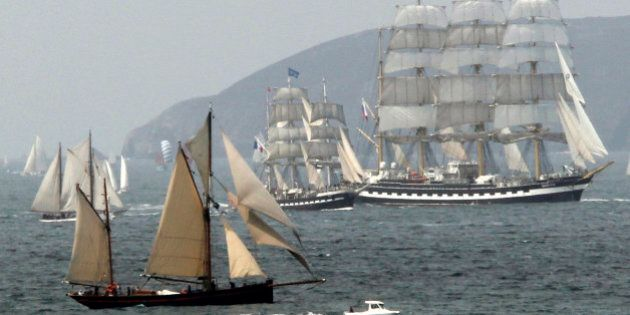 The four-masted Russian tall ship Kruzenshtern (R) is flanked by the French tall ship Bellem (C) as they...