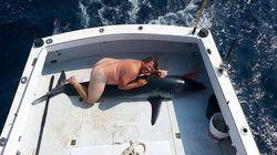 Nudo e sorridente su uno squalo morto, la foto che ha fatto indignare i