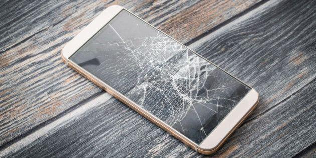 Modern broken mobile phone on wooden