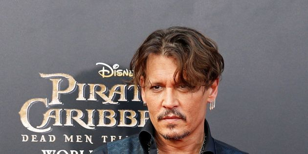 Actor Johnny Depp arrives on the red carpet for the global premiere of the