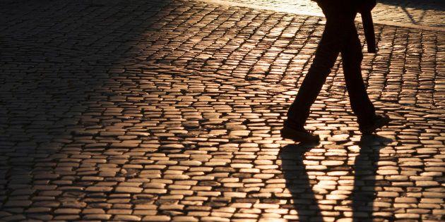 Shadow of man crossing cobblestone