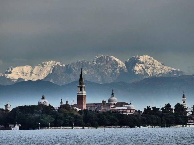 Nevica sulle montagne sopra Venezia, le foto della laguna sono uno