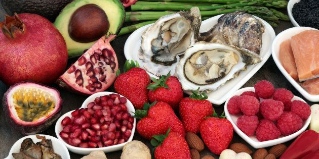 Aphrodisiac food in heart shaped dishes and loose over marble