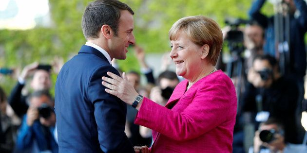 German Chancellor Angela Merkel and French President Emmanuel Macron shake hands as they arrive at a...