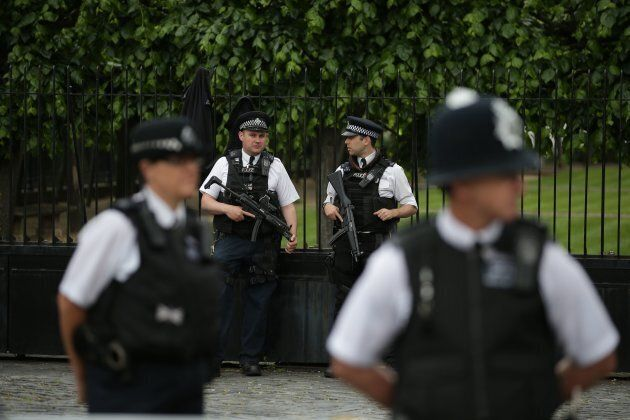 Armed British Police officers stand on duty outside of the Houses of Parliament in Westminster, central...