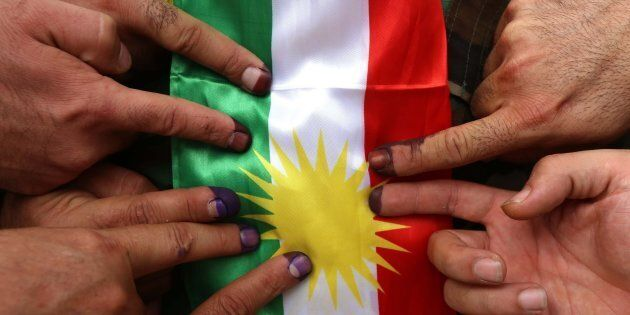 Members of a Kurdish Peshmerga battalion show their ink-stained fingers in front of a Kurdish flag after...