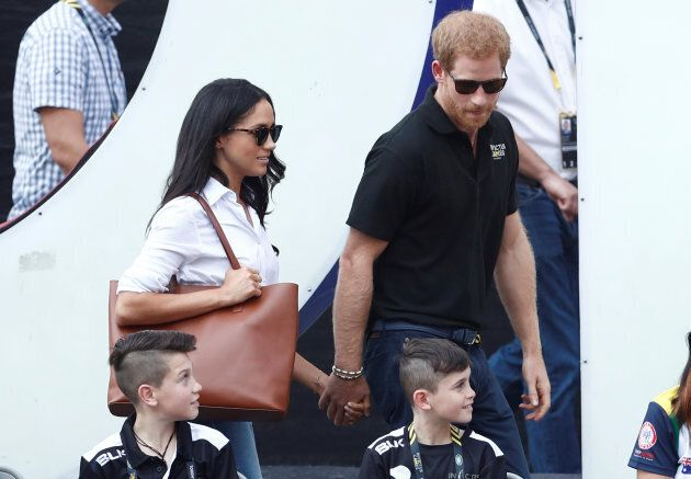 Britain's Prince Harry (R) arrives with girlfriend actress Meghan Markle at the wheelchair tennis event...