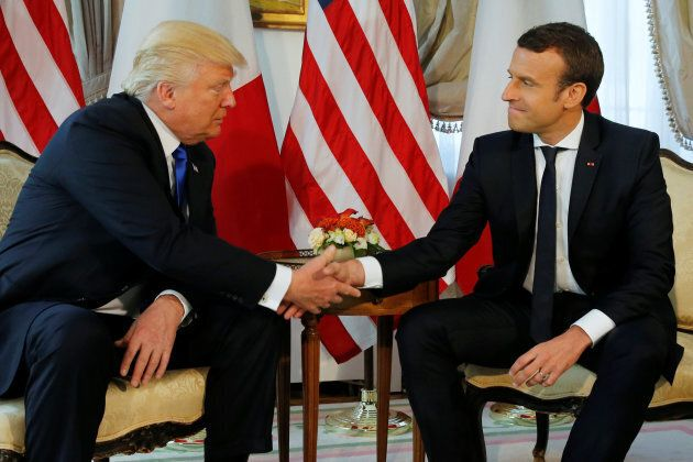 U.S. President Donald Trump (L) and French President Emmanuel Macron shake hands before a working lunch...