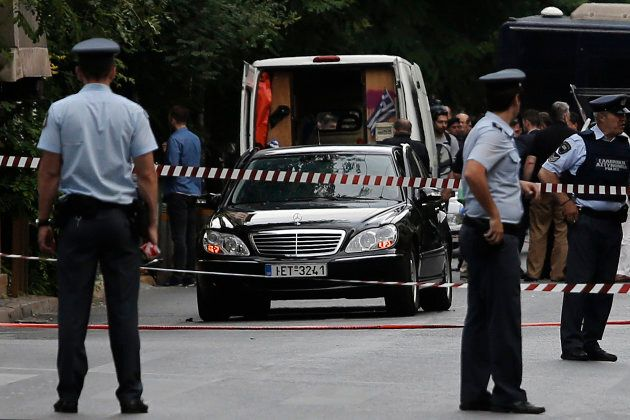 Police secure the area around the car of former Greek prime minister and former central bank chief Lucas...