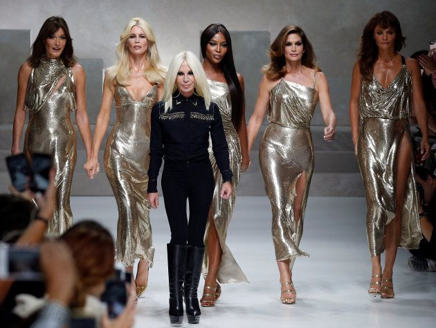 Italian designer Donatella Versace (3L) acknowledges the applause with former top models Carla Bruni...