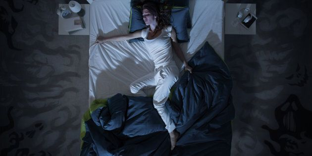 Nervous woman suffering from insomnia and lying in bed late at night, she is awake and restless, top