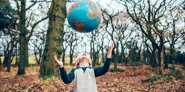 Little boy outdoors in the woods throwing a globe up in the