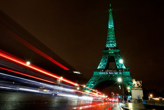 The Eiffel tower is illuminated in green with the words