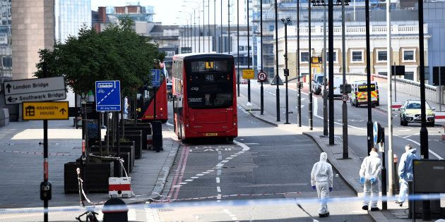 Police forensics investigators work on London Bridge near abandoned buses after an attack left 6 people...