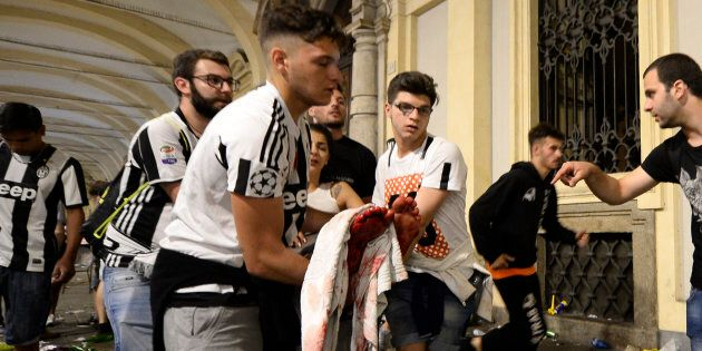 Juventus' supporters carry an injured woman in Piazza San Carlo after a panic movement in the fanzone...