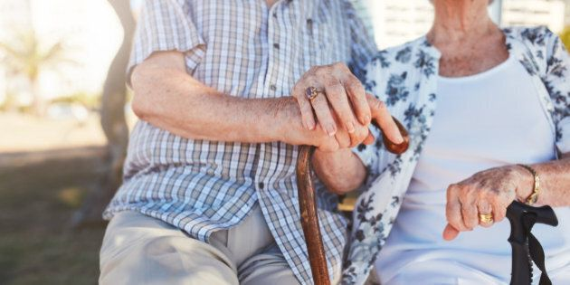 Close up of senior couple holding hands while sitting on the park bench together. Retired man and woman...