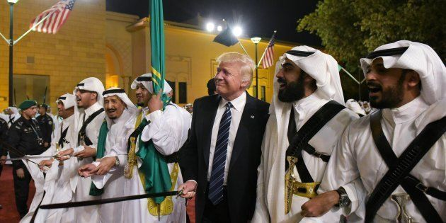 US President Donald Trump joins dancers with swords at a welcome ceremony ahead of a banquet at the Murabba...