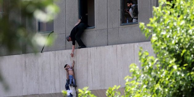 A boy is evacuated during an attack on the Iranian parliament in central Tehran, Iran, June 7, 2017....