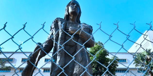 A statue of Christopher Columbus at a downtown Los Angeles park is surrounded by a chain-link fence on...
