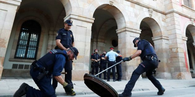 Officers of Catalonia's regional police force, Mossos D'esquadra, search unded a manhole cover outside...