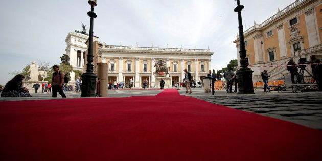 Workers lay a red carpet in front of the city
