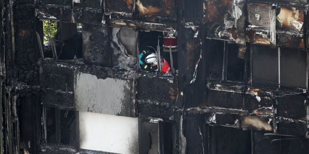 A firefighter examines material in a tower block severely damaged by a serious fire, in north Kensington,...