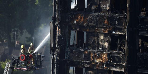 Firefighters spray water onto the Grenfell Tower block which was destroyed in a disastrous fire, in north...