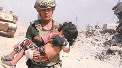 Si lancia sotto il fuoco dell'Isis per salvare una bambina: l'immagine fa il giro del