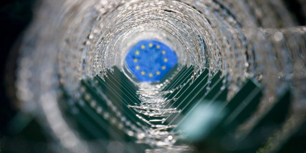 Concept image of a tunnel made of barbed wire and European Union flag at the end of the
