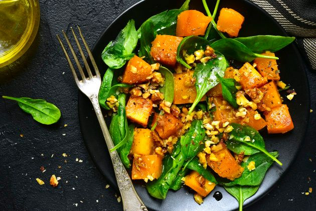Roasted pumpkin salad with spinach and walnut on a black plate on a stone background.Top