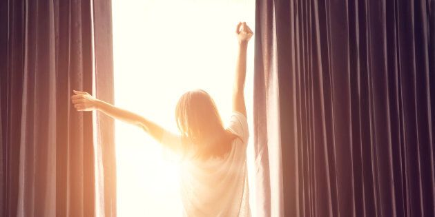 Woman standing near the window while stretching near bed after waking up with sunrise at morning, back