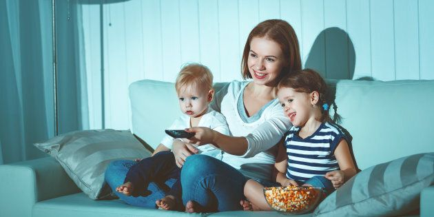 Family mother and children watching television at home on the