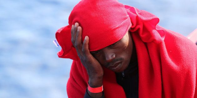 A migrant rests on the Vos Hestia ship after being rescued by