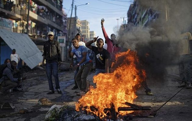 Opposition protesters taunt riot police to come and get them, as they stand behind a burning barricade...