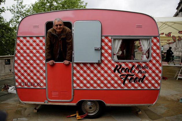 Photographer Martin Parr looks out from his own caravan which is serving food at the Photo London show...